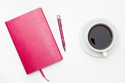 Cup of black coffee and diary with pen on white background. business minimal concept for women. Flat lay, top view.