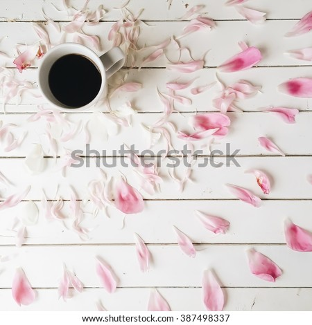 Cup of black coffee and pink peony petals on white wooden background. Overhead view. Flat lay, top view