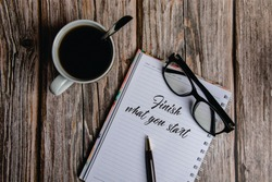 Cup of black coffee, eye glasses and note book with massage