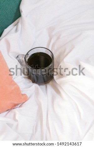 Cup of black coffee in clear glass mug on white comforter next to pink and teal pillows in bed, room service, copy space, cozy mornings