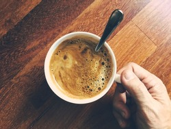 Cup of black coffee in male hand. Top view, vintage tonal correction, old instagram style filter effect