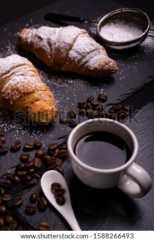 cup of black coffee in the foreground and croissants with veiled sugar on a dark background Foto d'archivio ©