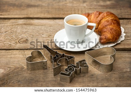 Cup of black coffee with croissant and heart decoration on rustic wooden background. romantic french breakfast