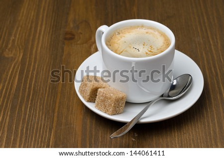 cup of black coffee with foam and cane sugar cubes, horizontal close-up