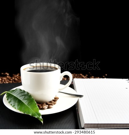 Cup of black coffee with mist with notebook, green coffee leaf, coffee beans at breakfast on black background