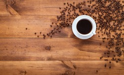 Cup of black morning coffee and cofee beans scattered on brown wooden table, espresso dark coffe aroma cafe shop background, warm hot beverage drink in mug, top view, flat lay, closeup copy space