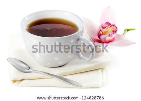 Cup of black tea and flower isolated on white
