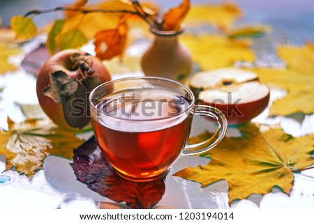 Cup of black tea, Apple slice and Apple, vase with birch twig with withered leaves on autumn maple leaves lying on glass. Shot with bokeh effect, objects in the distance are out of focus and blurred #1203194014