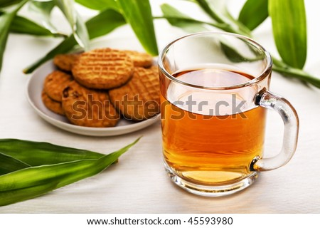 Cup of black tea, biscuits on a plate and green leaves as background