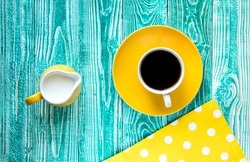 cup of black tea coffee cup on yellow plate and yellow milk jug on turquoise colored old wooden table with yellow napkin at polka dots, top view