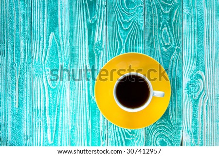 cup of black tea on yellow plate on turquoise colored old wooden table  top view #307412957
