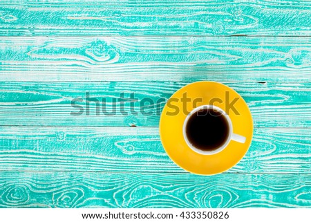 cup of black tea on yellow plate on turquoise colored old wooden table top view #433350826