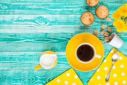 cup of black tea or coffee on yellow plate and yellow milk jug cane sugar, cakes, dandelions, teaspoon on turquoise colored wooden table with yellow napkin at polka dots, top view