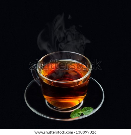 cup of black tea with mint on a black background isolated