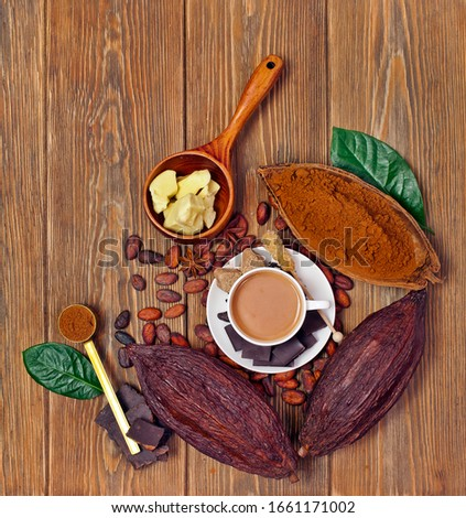 Cup of cacao drink with cocoa pods, cacao powder, cocoa butter, chocolate, sugar, cacao beans and natural green leaves on wooden background. Top view.