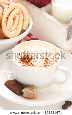 Cup of cappuccino and swiss roll for breakfast.