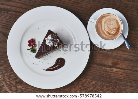 Cup of cappuccino coffee and piece of chocolate poppy cake on wooden table. Flatlay or top view. #578978542