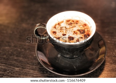 Cup of cappuccino coffee decorated with chocolate on dark table