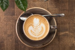 Cup of cappuccino coffee isolated on wooden background