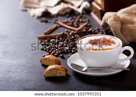 Cup of cappuccino coffee on dark table #1037995351
