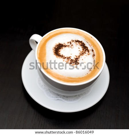 cup of cappuccino coffee on saucer, chocolate heart on top, copy space