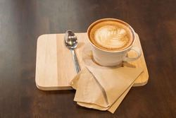 Cup of cappuccino coffee on wooden background.