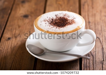 Cup of cappuccino coffee on wooden table #1074209732