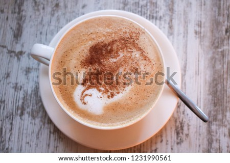 Cup of cappuccino coffee on wooden table. #1231990561
