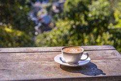 Cup of cappuccino coffee on wooden table bokeh annd blur village background