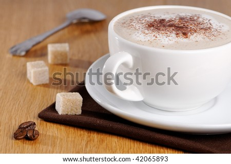 Cup of cappuccino coffee with brown sugar cubes on wooden table
