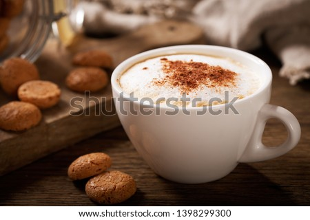 cup of cappuccino coffee with cookies on wooden table