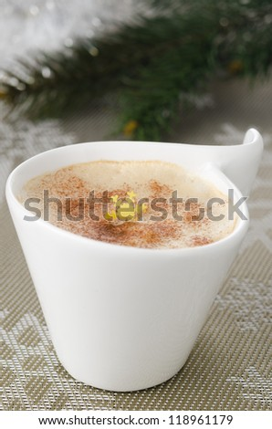 Cup of cappuccino on the table, fir branches in the background