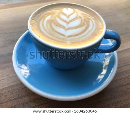Cup of cappuccino on wood table with heart on coffee crema.