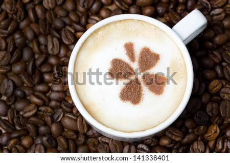 cup of cappuccino with cinnamon pattern on a background of coffee beans, horizontal close-up