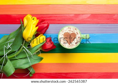 Cup of cappuccino with heart shape and bouquet of tulips on multicolor background.