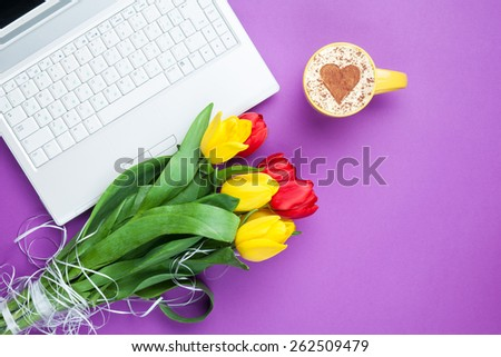 Cup of cappuccino with heart shape and computer, tulips on violet background.