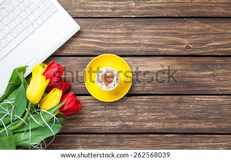 Cup of cappuccino with heart shape and computer, tulips on wooden background.