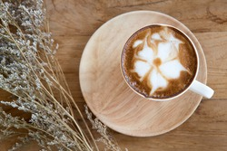 Cup of cappuccino with latte art on a wooden plate and wooded table  decorated with dried glass flower on the side