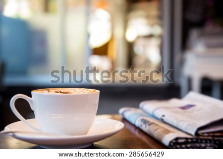 Cup of cappuccino with newspaper on the table, coffee shop background