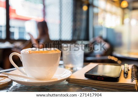 Cup of cappuccino with note book and pen, blur coffee shop background