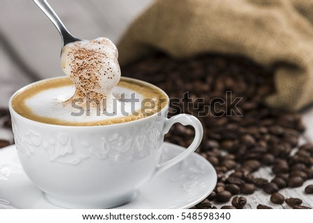 Cup of Cappuccino with Spoon and Foam / Composition of Cup of Cappuccino and spoon with foam, sack of coffee beans on white wooden table  #548598340