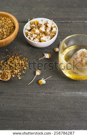 cup of chamomile tea with different size dried flowers on black wood table