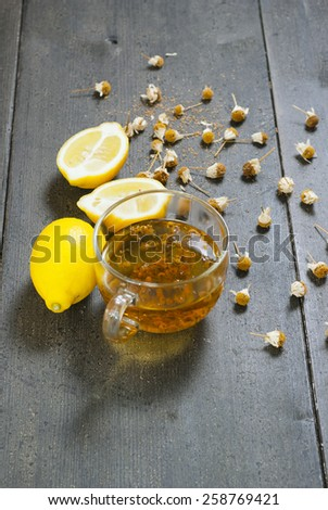 cup of chamomile tea with dried flowers and lemons on black wood table