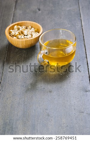 cup of chamomile tea with dried flowers on black wood table