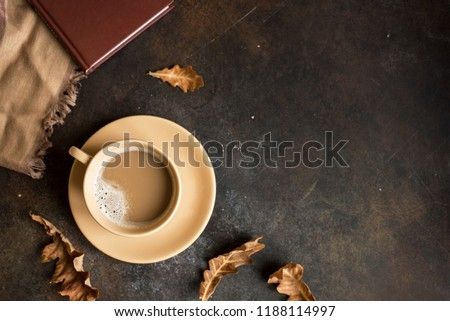 Cup of cocoa, book and autumn leaves on rustic brown background, top view. Seasonal cozy autumn hot drink, relax concept.