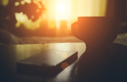 Cup of coffe or tea with phone on the home bedroom wood table in sunset time with soft light