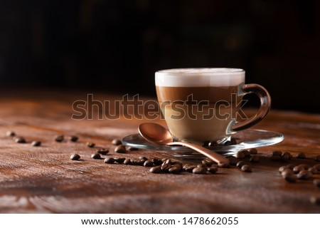 Cup of coffe with milk on a dark background. Hot latte or Cappuccino prepared with milk on a wooden table with copy space