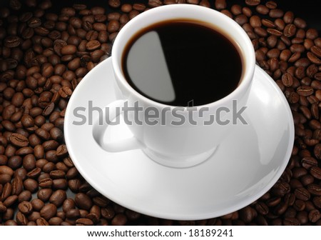 Cup of coffee. A background with coffee grains and a white cup