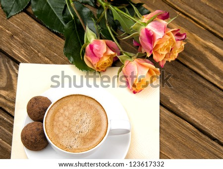 cup of coffee and a bouquet of roses with chocolates on a wooden table.