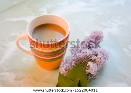 cup of coffee and a branch of flowers liliac